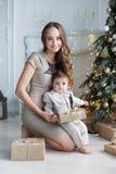Mamá con un pequeño hijo cerca de un árbol de navidad hermoso en su casa Imagen de archivo libre de regalías