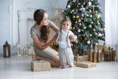 Mamá con un pequeño hijo cerca de un árbol de navidad hermoso en su casa Fotografía de archivo