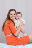 Mamá con una hija de seis meses que se sienta en cama fotos de archivo