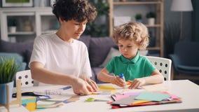 Mamá creativa de la familia y pequeño niño que hacen los collages con el papel, las tijeras y el pegamento almacen de video