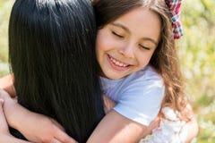 Mamá de abarcamiento de la muchacha alegre en prado Imagen de archivo libre de regalías