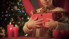 Mamá de amor que da el regalo de Navidad a la muchacha sorprendida, víspera del día de fiesta que espera almacen de video