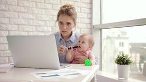 Mamá de funcionamiento con el niño en la tabla Empresaria que detiene a la niña pequeña a mano almacen de metraje de vídeo