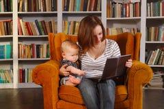 Mamá de funcionamiento La mujer bastante joven y su niño del bebé están practicando surf Internet con el transformador de la tabl imagen de archivo