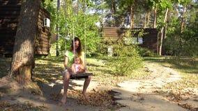 Mamá de la mujer con la muchacha en la oscilación de madera debajo del árbol metrajes