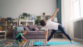 Mamá deportiva que hace la yoga que estira el cuerpo mientras que niño que juega con la construcción de los bloques almacen de video