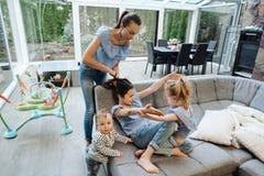 Mamá, dos hijas y un pequeño hijo en el sofá Imagen de archivo libre de regalías