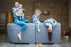 Mamá, dos hijas y un pequeño hijo en el sofá Imagenes de archivo