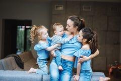 Mamá, dos hijas y un pequeño hijo en el sofá Fotografía de archivo libre de regalías