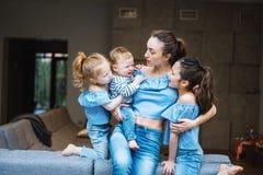 Mamá, dos hijas y un pequeño hijo en el sofá Fotografía de archivo
