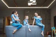 Mamá, dos hijas y un pequeño hijo en el sofá Imágenes de archivo libres de regalías