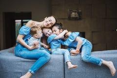 Mamá, dos hijas y un pequeño hijo en el sofá Foto de archivo