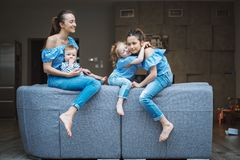 Mamá, dos hijas y un pequeño hijo en el sofá Fotos de archivo libres de regalías