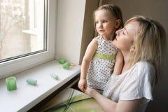 Mamá e hija 3 años que se sientan en la ventana fotografía de archivo libre de regalías