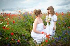 Mamá e hija con las flores salvajes entre las flores del campo Foto de archivo