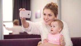 Mamá e hija de Selfie en casa Mujer hermosa con el niño que toma la foto del teléfono almacen de metraje de vídeo