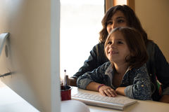 Mamá e hija en el ordenador fotografía de archivo