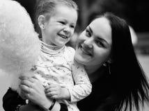 Mamá e hija en el parque que comen el caramelo de algodón Foto de archivo