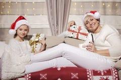 Mamá e hija en el sofá con los presentes Foto de archivo libre de regalías