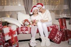 Mamá e hija en el sofá con los presentes Fotos de archivo