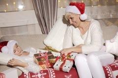 Mamá e hija en el sofá con los presentes Imagen de archivo libre de regalías