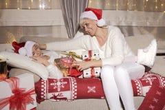 Mamá e hija en el sofá con los presentes Foto de archivo