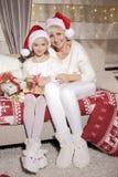 Mamá e hija en el sofá con los presentes Imágenes de archivo libres de regalías