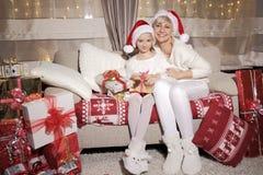 Mamá e hija en el sofá con los presentes Fotografía de archivo libre de regalías