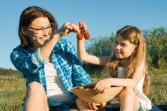Mamá e hija en la naturaleza, los días de fiesta del país del verano, la madre y el niño sentándose en la hierba que come las fre imágenes de archivo libres de regalías