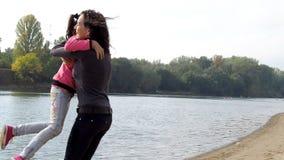 Mamá e hija en la orilla del río La mamá abraza a su hija en el río La familia está abrazando T metrajes