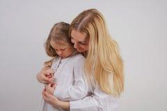 Mamá e hija en las camisas blancas con el pelo rubio largo que presenta en un fondo sólido en el estudio la familia encantadora fotos de archivo