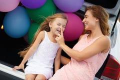 Mamá e hija en un coche con los globos Fotos de archivo libres de regalías