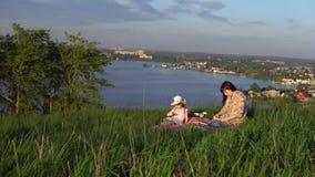 Mamá e hija en una comida campestre en una colina cerca de la charca almacen de metraje de vídeo