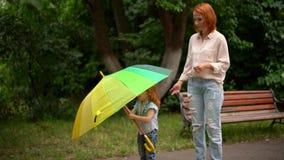 Mamá e hija felices debajo del paraguas coloreado almacen de video