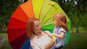 Mamá e hija felices debajo del paraguas coloreado metrajes