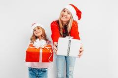 Mamá e hija felices, en los sombreros de Papá Noel y los suéteres de la Navidad fotos de archivo