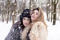 Mamá e hija que abrazan cada uno con amor en la nieve Foto de archivo libre de regalías