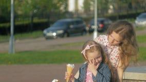 Mamá e hija que comen el helado en un parque Madre y niño familia feliz relajante almacen de video