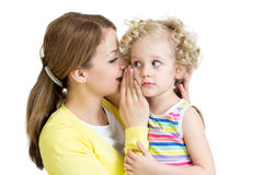 Mamá e hija que comparten un susurro secreto Imagen de archivo libre de regalías