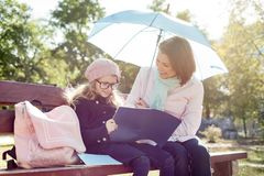 Mamá e hija que hablan, el sentarse de risa en el banco en el parque, niño con el cuaderno de la lectura del bolso de escuela fotos de archivo