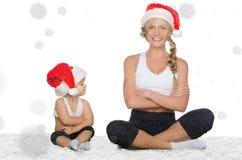 Mamá e hija que hacen yoga debajo de nieve que cae Imágenes de archivo libres de regalías