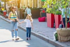 Mamá e hija que llevan a cabo las manos que caminan alrededor de la ciudad imágenes de archivo libres de regalías
