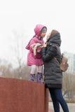 Mamá e hija que se besan en la naturaleza en la primavera imágenes de archivo libres de regalías