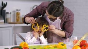 Mamá e hija que se divierten que hace la ensalada en cocina almacen de metraje de vídeo