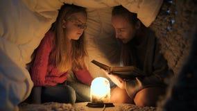Mamá e hija que se sientan bajo la manta y lectura almacen de video
