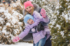 Mamá e hija que tienen mirada de cinco años de la diversión hacia fuera para los árboles Fotografía de archivo