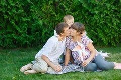 Mamá e hijo del papá que se sientan en una manta en el parque y el beso Foto de archivo