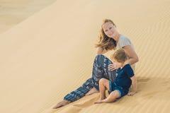 Mamá e hijo en el desierto El viajar con concepto de los niños foto de archivo