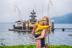 Mamá e hijo en el fondo de Pura Ulun Danu Bratan, Bali Templo hindú rodeado por las flores en el lago Bratan, Bali fotos de archivo libres de regalías