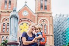 Mamá e hijo en la catedral de Notre Dame de Saigon del fondo, BU imagenes de archivo